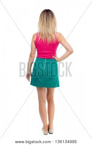 back view of standing young beautiful  woman.  girl  watching. Rear view people collection.  backside view of person.  The blonde in a green skirt and pink blouse is resting his left hand side.