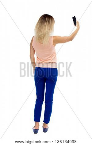 back view of standing young beautiful  woman  and using a mobile phone. girl  watching. Rear view people collection.  Blonde in blue pants makes self holding the phone in your left hand.