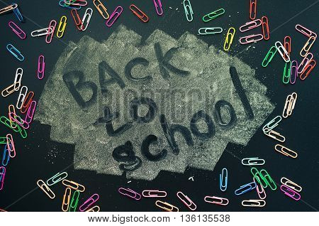 Back to school concept. Colorful clips on blackboard background. Back to school concept with colorful clips. Schoolchild and student studies accessories. Top view.
