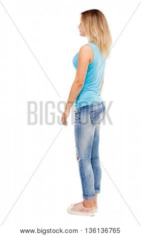 back view of standing young beautiful  woman. girl  watching. Rear view people collection.  backside view of person.  Isolated over white background. girl in jeans and a blue t-shirt standing sideways