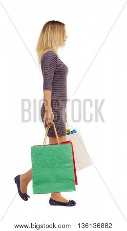 back view of going  woman  with shopping bags . backside view of person.  Rear view people collection. Isolated over white background. Girl in a short dress is left with colorful bags.