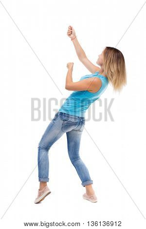 back view of standing girl pulling a rope from the top or cling to something. backside view of person. blonde in a blue shirt and jeans, he pulls the top rope for turning right side.