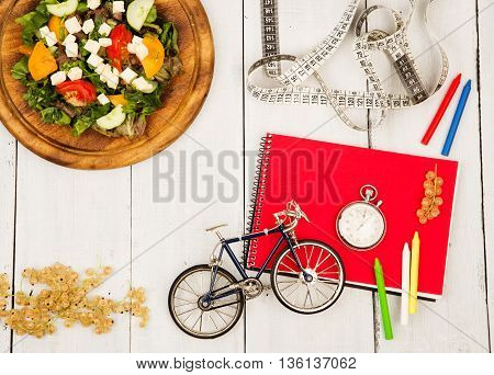 Bicycle Model, Salad Of Fresh Vegetables, Red Notepad, Stopwatch And Tape Measure On A White Wooden