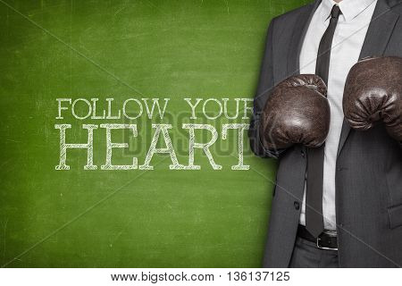 Follow your heart on blackboard with businessman wearing boxing gloves