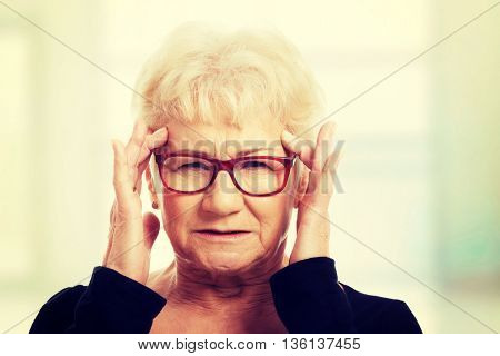 An old woman is eye glasses is having a headache.