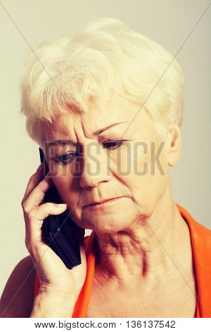 An old lady talking through phone.