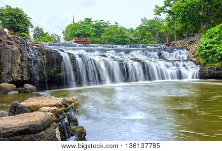 Rock waterfall with water flowing down smooth as silk sheet stone steps making natural scenery here beautiful and lyrical, idyllic countryside in Vietnam