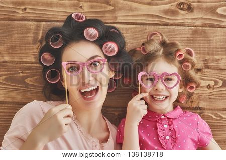 Funny family! Mother and her child daughter girl with a paper accessories.