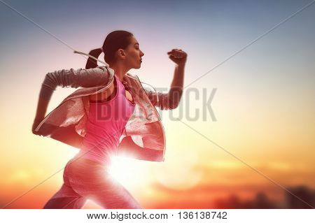 Athletic young woman running in the nature. Healthy lifestyle.