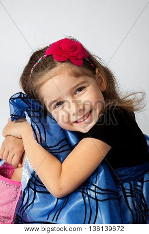 A sweet little girl hugs her knees while posing for a portrait.