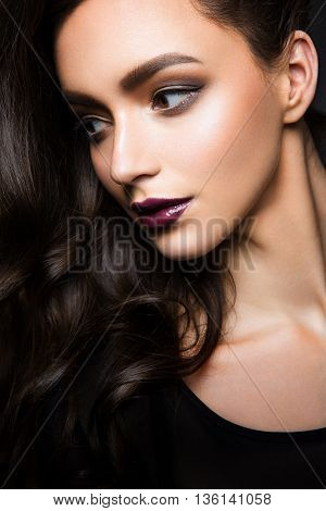 Glamour portrait of beautiful woman model with fresh daily makeup and romantic wavy hairstyle. Fashion shiny highlighter on skin, sexy gloss lips make-up and dark eyebrows