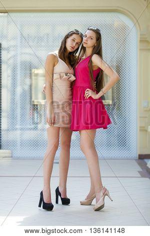 Two beautiful brunette women in summer dresses. Studio portrait