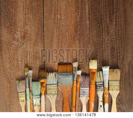 Brushes, paint, palette, canvas on wood background