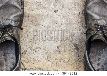 the old genuine leather shoes on concrete background focus on concrete
