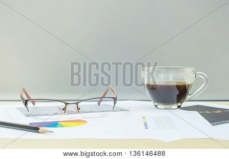 Closeup black coffee in transparent cup of coffee with work paper on blurred wooden desk and frosted glass wall textured background work concept by coffee work paper eyeglasses and pencil