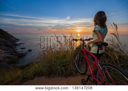 Young lady standing on top of a hill with bicycle and enjoying the sunset over sea
