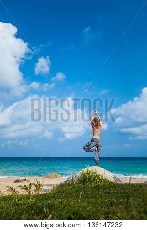 Lady stretching on the stone near sandy beach with ocean
