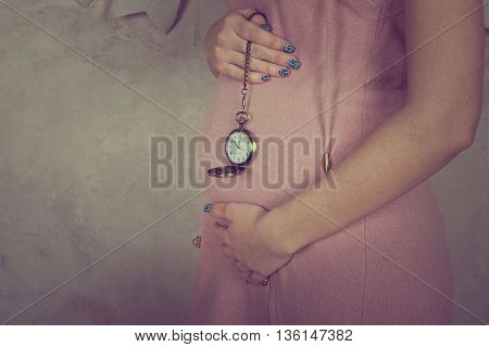 pregnant woman's belly with an antique clock