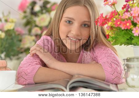Beautiful  teenager girl reading magazine at home with tea
