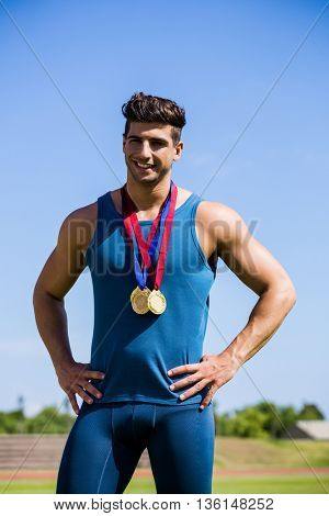 Happy athlete posing with gold medals around his neck