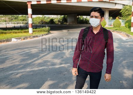Portrait of young man in face mask having allergy