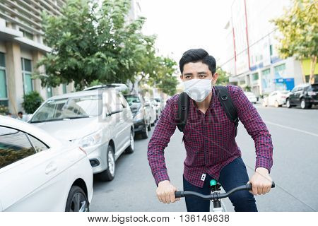 Young guy in face mask riding bike in the street