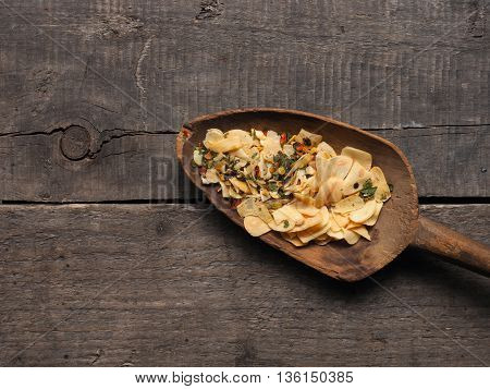 Slices of dried garlic with spicy herbs on an old used wooden spoon Italian cooking ingredients