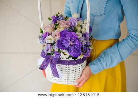 girl holding beautiful purple bouquet of mixed flowers in basket no face