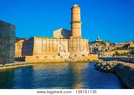 The big watchtower is reflected in blue water of the Marseilles port. Saint Ioann's fort