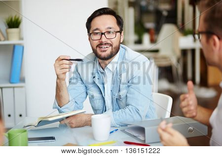 Young businessman communicating with his colleague at the table