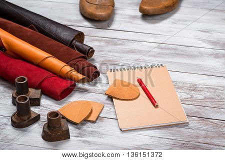 Brightly colored leather in rolls, working tools, shoe lasts, notebook with pencil on white wooden background. Leather craft.