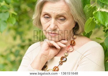 Nice sad old woman on the spring background