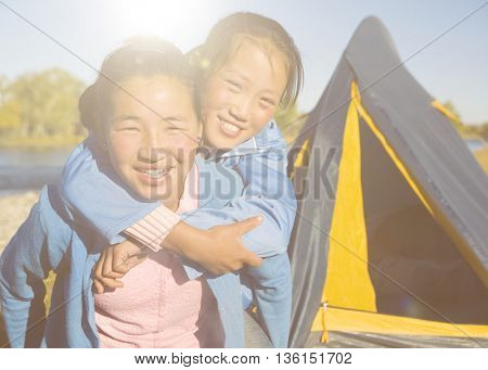 Happy Mongolian girls playing piggyback at campsite.