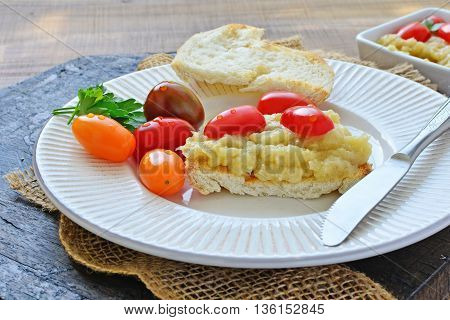 Roasted eggplant puree spread on toasted bread with cherry tomatoes on white plate.