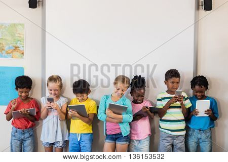 Pupils standing with technology in classroom
