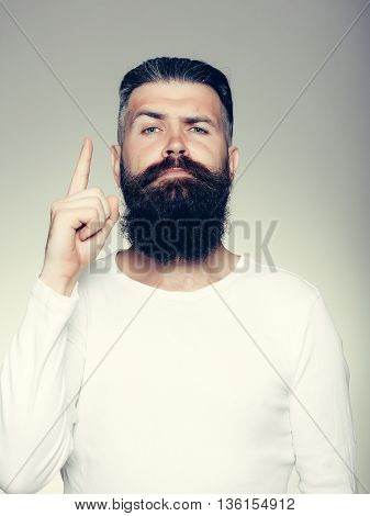handsome young man with long beard and moustache on face with raised finger on grey background in studio