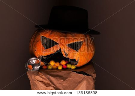 orange halloween pumpkin with scary face and black hat with colorful dragee candies in mouth and plastic cup on paper on brown background