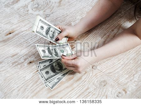 Woman hands with dollars on a wooden background. Cash in hands. Money in hands. Fake money. Shallow depth of field. Selective focus.
