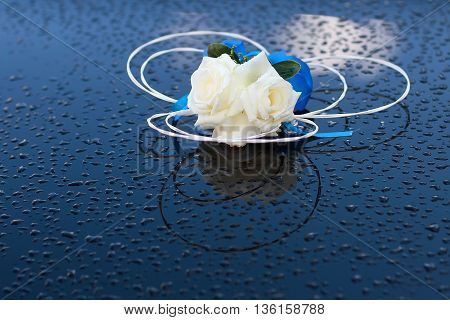 Wedding boutonniere with white roses beautiful floral decoration on wet dark background
