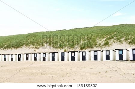 Beach huts or houses and blue sky. Beach bathing huts with white sand and clear blue sky. Beach scene with copy space. Side view.