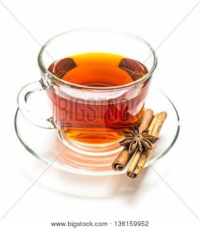 Transparent cup of black tea cinnamon steaks and anise star isolated on white background
