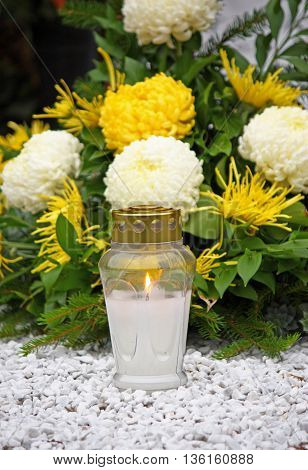 Flowers and votive candle which glows on the grave lantern