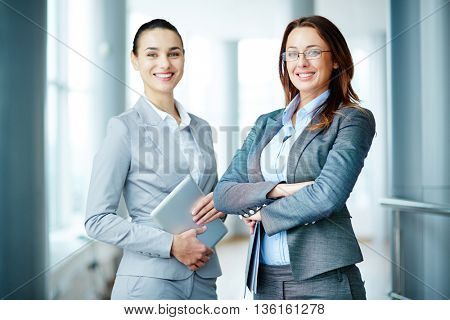 Portrait of two young businesswomen colleagues in an office