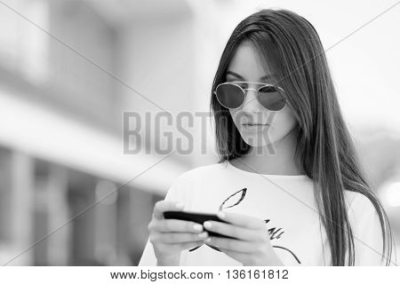 Woman Walking And Using A Smart Phone In The Street Sunny Summer Day
