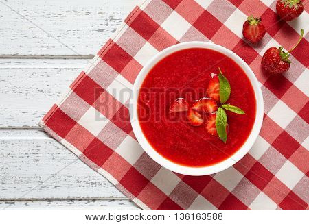 Natural organic fresh raw strawberry cream soup vegetarian cold sweet berry smoothie summer food on white wooden background table
