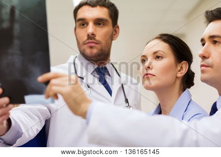 clinic, people, healthcare and medicine concept - group of medics with spine x-ray scan at hospital