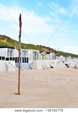 Beach huts or houses and blue sky. Multicolored beach bathing huts with white sand and clear blue sky. Beach scene with copy space. Side view of beach huts in a row.