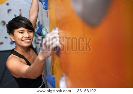 Portrait of lovely young Vietnamese girl enjoying climbing