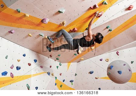 Young dexterous woman climber practicing in gym