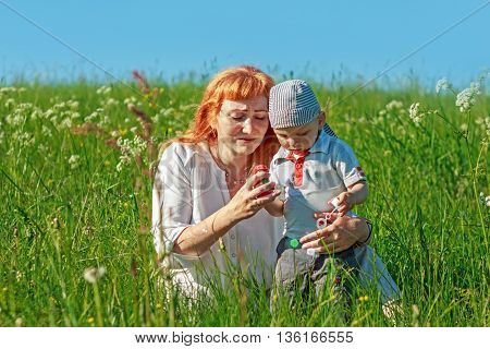 Beautiful red-haired mother playing with her baby in the field. Family fun outdoors.